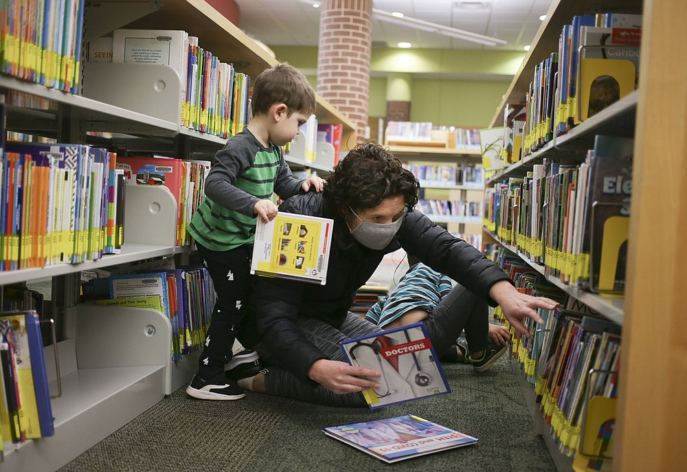 Danielle Sanders of Bentonville (center), picks out books with sons  Tyler Sanders, 3, (left) and Henry Sanders, 4, (rear), Thursday, January 21, 2021 at the Bentonville Library in Bentonville. Bentonville residents could be asked to approve $266 million in bonds for street and park improvements as well as other capital projects in the city. Library plans call for 6,400-square-foot addition and renovations to 10,000 square feet of the interior of the building. The addition would include a children's expansion, which would include a larger story time area and larger craft space. There would also be a teen space and maker space. Check out nwaonline.com/210119Daily/ for today's photo gallery.  (NWA Democrat-Gazette/Charlie Kaijo)