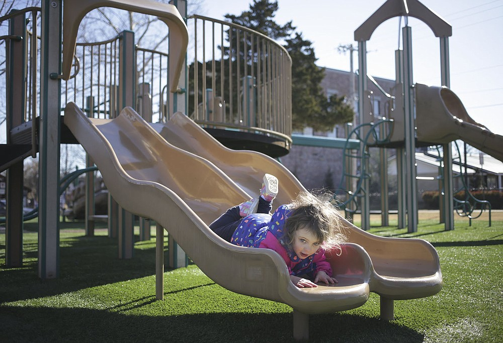 Lynette Henley, 3, of Springdale rides down a slide,Friday, January 23, 2022 at Dave Peel Park in Bentonville. Bentonville residents could be asked to approve $266 million in bonds for street and park improvements as well as other capital projects in the city. The renovations at Dave Peel Park would include the playground, restroom and plaza area. Check out nwaonline.com/210119Daily/ for today's photo gallery.  (NWA Democrat-Gazette/Charlie Kaijo)