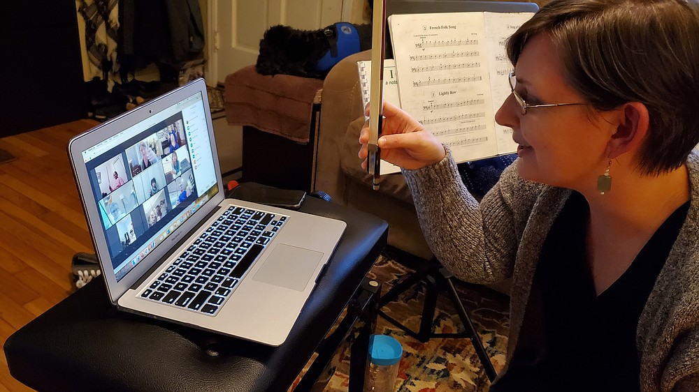 Joanna Klett, Sturgis Music Academy education coordinator, shows cello students how her fingers hold the bow via Zoom in January.  (Special to the Democrat-Gazette/Thomas McDonald)