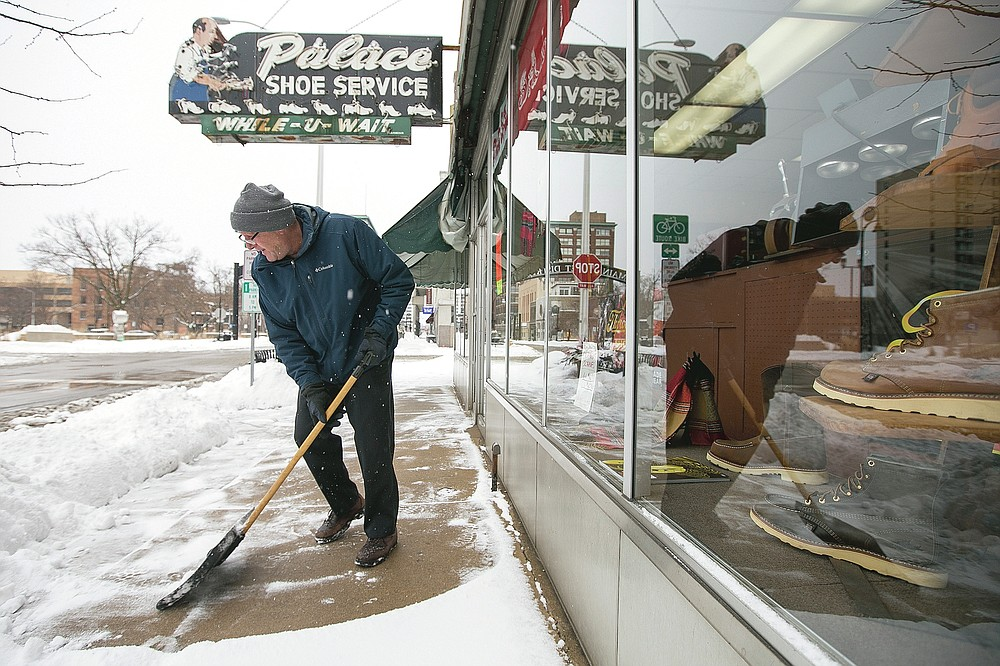 Tom Giamalva, owner of Palace Show Services, clears away snow from the sidewalk in front of his business on North Main Street on Tuesday, Jan. 26, 2021, after a snowstorm in Rockford, Ill. Many schools and businesses closed as the storm moved across the Midwest and officials urged drivers to stay off the roads.  (Scott P. Yates/Rockford Register Star via AP)