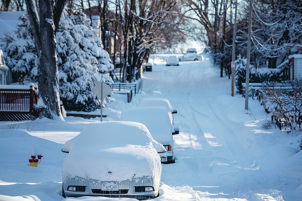 Snow covers cars and Blondo Street east of Northwest Radial Highway in Omaha, Neb., on Tuesday, Jan. 26, 2021. The Omaha area recorded almost 12 inches of snow the day before. (Chris Machian/Omaha World-Herald via AP)