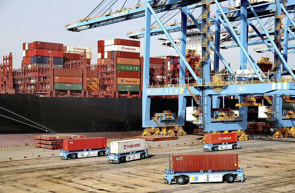 Automated vehicles move shipping containers in a container port in Qingdao in eastern China's Shandong Province, Thursday, Jan. 12, 2021. The U.S.-Chinese trade war isn't going away under President Joe Biden. Biden won't confront Beijing right away, economists say, because he needs to focus on the coronavirus and the economy. However, Biden looks set to renew pressure over trade and technology complaints that prompted President Donald Trump to hike tariffs on Chinese imports in 2017. (Chinatopix via AP)