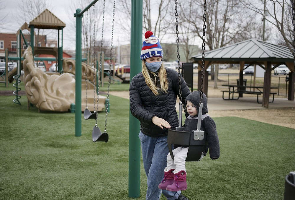 Mackenzie Portwood puts Penelope Portwood, 2, on a swing Friday at Dave Peel Park in Bentonville. Bentonville is looking at a $266 million bond project for street and park improvements as well as other capital projects in the city.   (NWA Democrat-Gazette/Charlie Kaijo)