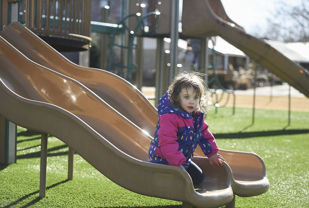 Lynette Henley, 3, of Springdale rides down a slide,Friday, January 23, 2022 at Dave Peel Park in Bentonville. Bentonville residents could be asked to approve $266 million in bonds for street and park improvements as well as other capital projects in the city. The renovations at Dave Peel Park would include the playground, restroom and plaza area.  (NWA Democrat-Gazette/Charlie Kaijo)