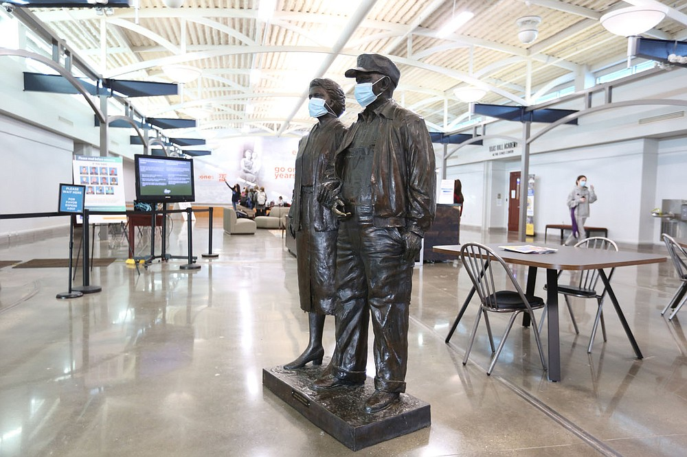 The statues of Harvey and Bernice Jones are visible Friday, January 15, 2021, inside the lobby are of the Jones Center in Springdale. The Downtown Springdale Alliance is sponsoring public events for the public to share their visions of a reimagined Jones Center.  (NWA Democrat-Gazette/David Gottschalk)
