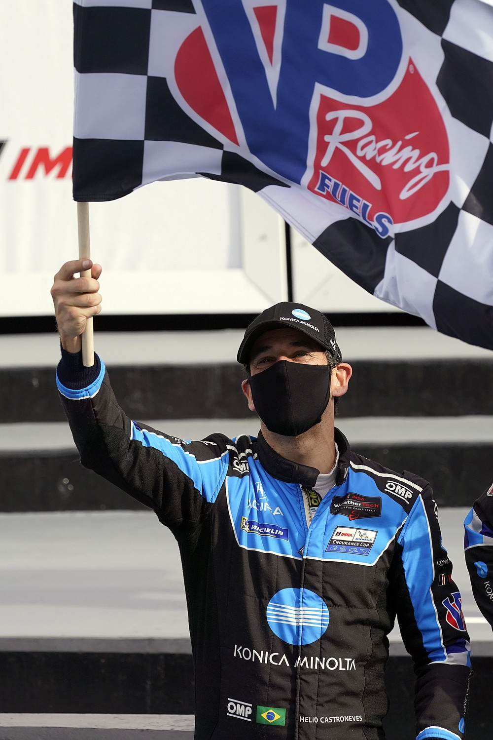 Helio Castroneves waves the checkered flag after he and driving teammates Ricky Taylor, Filipe Albuquerque and Alexander Rossi won the Rolex 24 hour auto race at Daytona International Speedway, Sunday, Jan. 31, 2021, in Daytona Beach, Fla. (AP Photo/John Raoux)