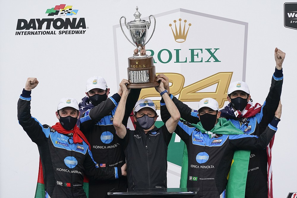 The Konica Minolta racing team, from left to right, Filipe Albuquerque, Alexander Rossi, team owner Wayne Taylor, Helio Castroneves and Ricky Taylor celebrate with the championship trophy after winning the Rolex 24 hour auto race at Daytona International Speedway, Sunday, Jan. 31, 2021, in Daytona Beach, Fla. (AP Photo/John Raoux)