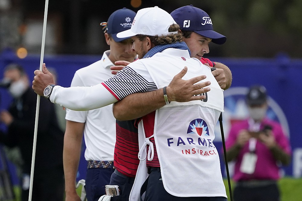 Patrick Reed, facing right, hugs his caddie, Kessler Karain, after putting on the 18th hole on the South Course to win the Farmers Insurance Open golf tournament at Torrey Pines, Sunday, Jan. 31, 2021, in San Diego. (AP Photo/Gregory Bull)