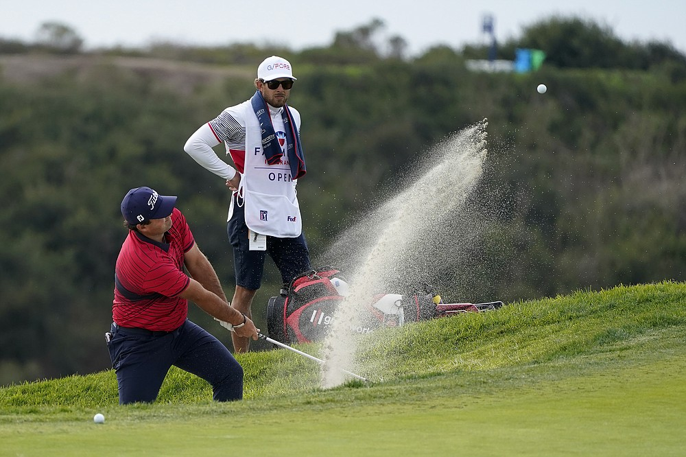 Patrick Reed hits from a bunker toward the 14th hole on the South Course during the final round of the Farmers Insurance Open golf tournament at Torrey Pines, Sunday, Jan. 31, 2021, in San Diego. (AP Photo/Gregory Bull)