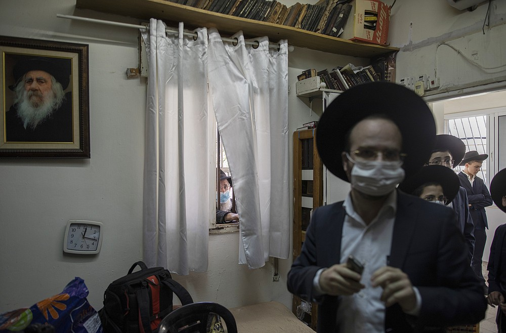 Followers of Rabbi Chaim Kanievsky line up at his home to receive a blessing or to ask questions, which he answers for a few hours a day, in Bnei Brak, Israel, Jan. 24, 2021. Kanievsky is the spiritual authority for hundreds of thousands of ultra-Orthodox Jews, but his pronouncements on the coronavirus have made him a villain to many. (Dan Balilty/The New York Times)