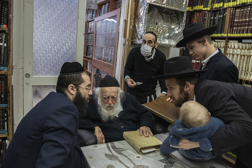Yaakov Kanievsky, left, listens to a family's request for a blessing before repeating it to his grandfather, Rabbi Chaim Kanievsky, at his home in Bnei Brak, Israel, Jan. 24, 2021. Rabbi Kanievsky is the spiritual authority for hundreds of thousands of ultra-Orthodox Jews, but his pronouncements on the coronavirus have made him a villain to many. (Dan Balilty/The New York Times)