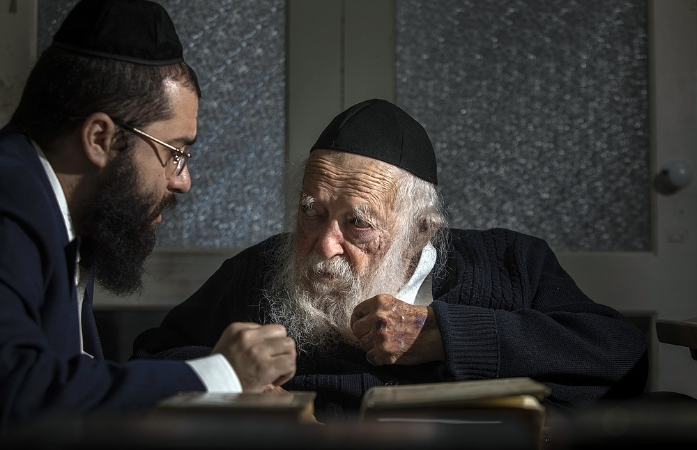 Rabbi Chaim Kanievsky, center, whose pronouncements have made him one of the most controversial figures in Israel today, with his grandson Yaakov Kanievsky, at the rabbi's home in Bnei Brak, Israel, Jan. 24, 2021. Kanievsky is the spiritual authority for hundreds of thousands of ultra-Orthodox Jews, but his pronouncements on the coronavirus have made him a villain to many. (Dan Balilty/The New York Times)