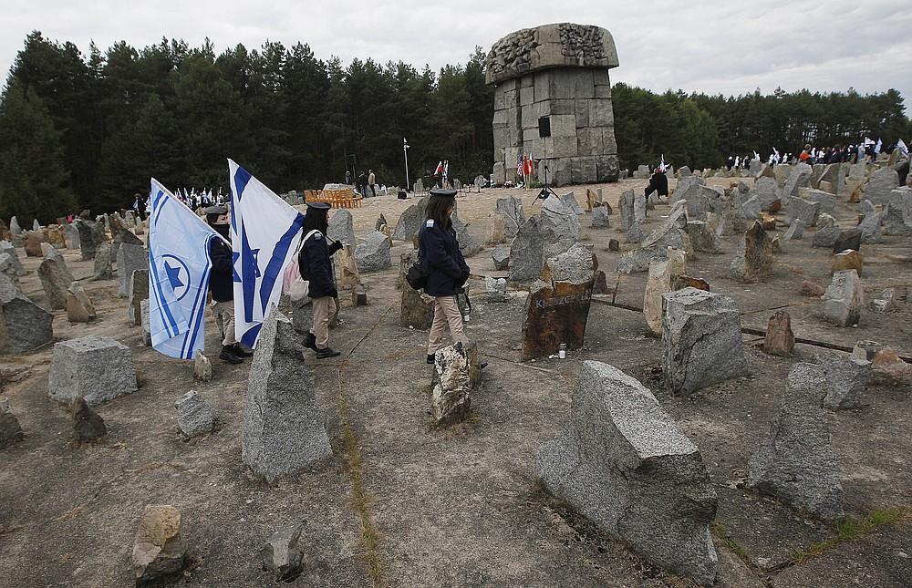 PLIK _ Na tym pliku zdjęcie ze środy, 2 października 2013 r., Izraelska młodzież maszeruje ze swoimi flagami narodowymi obok pomnika około 900 000 europejskich Żydów, którzy zostali zabici przez nazistów w latach 1941-1944 w obozie zagłady i pracy w Treblince przy pomniku w Treblince .  Polska.  Dwóch polskich historyków stoi w obliczu pomówienia za naukowe badanie polskiego zachowania podczas II wojny światowej.  Ten przypadek może przesądzić o losach niezależnych badań nad Holokaustem pod nacjonalistycznym rządem Polski.  Werdykt spodziewany jest 9 lutego.  (AP Photo / Czarek Sokolowski, File)