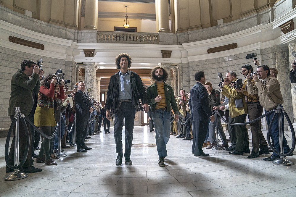 """This image released by Netflix shows Sacha Baron Cohen, center left, and Jeremy Strong in a scene from """"The Trial of the Chicago 7."""" (Niko Tavernise/Netflix via AP)"""