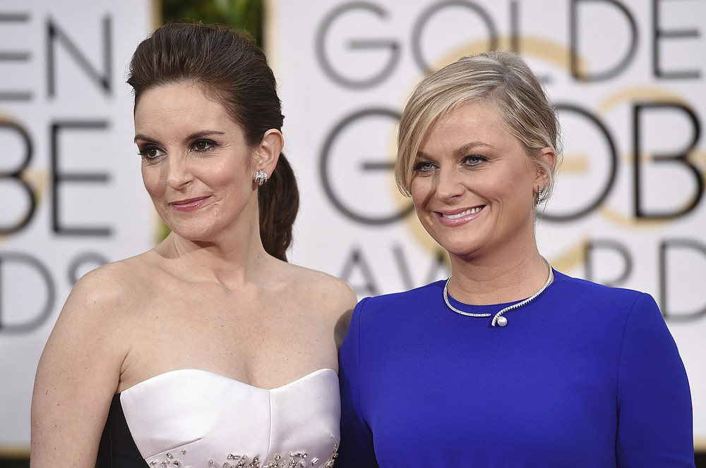 FILE - In this Jan. 11, 2015, file photo, Tina Fey, left, and Amy Poehler arrive at the 72nd annual Golden Globe Awards in Beverly Hills, Calif. The 78th Golden Globes will for the first time be held on two coasts, with Tina Fey live in New York and Amy Poehler in Beverly Hills, Calif., a person close to the show said Tuesday, Feb. 2, 2021, as the annual Hollywood ceremony adapts to the pandemic. (Photo by John Shearer/Invision/AP, File)