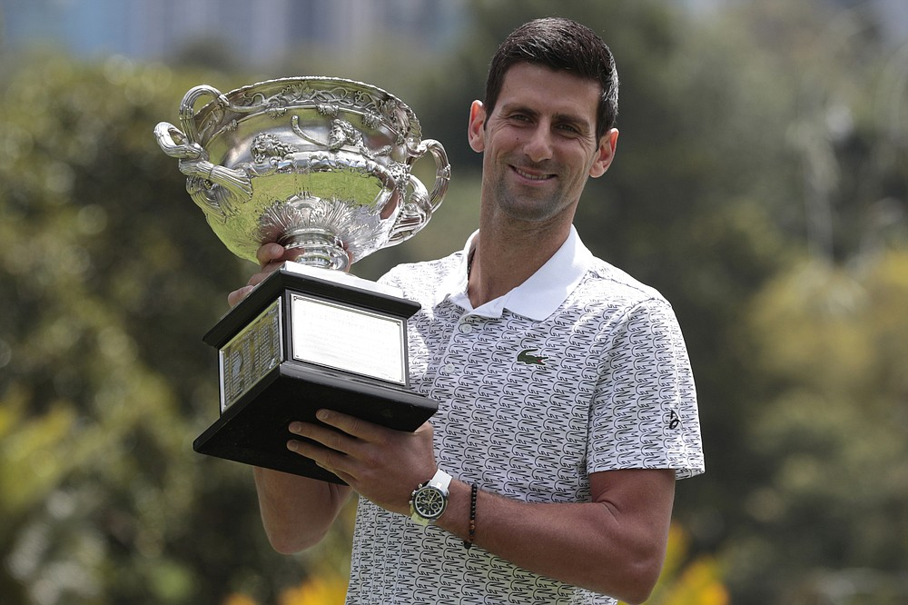 FILE - In this Monday, Feb. 3, 2020 file photo, Serbia's Novak Djokovic poses with his trophy, the Norman Brookes Challenge Cup, during a photo shoot at Melbourne's Royal Botanic Gardens following his win over Austria's Dominic Thiem in the men's singles final at the Australian Open tennis championships, in Melbourne, Australia. Australian Open starts the 2021 Grand Slam tennis season on Monday, Feb. 8, 2021 in Melbourne (Sunday in the United States), with a delay of three weeks because of the coronavirus pandemic. (AP Photo/Dita Alangkara, File)