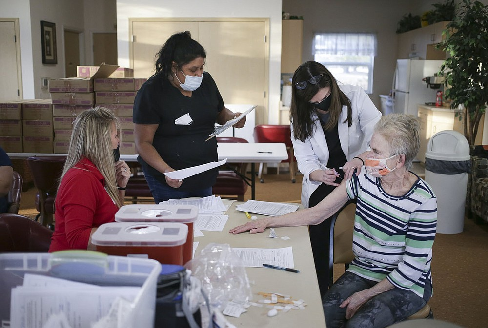 Nurse Brenna Neumann (third from left) administers a covid-19 vaccine to Gail Cawsey (right) as Tracy Schnick (from left) and Mary Avila process vaccine recipients, Friday, February 5, 2021 at Apple blossom retirement community in Rogers. Forty residents at Apple Blossom retirement community received their covid-19 vaccines. Check out nwaonline.com/210206Daily/ for today's photo gallery.  (NWA Democrat-Gazette/Charlie Kaijo)