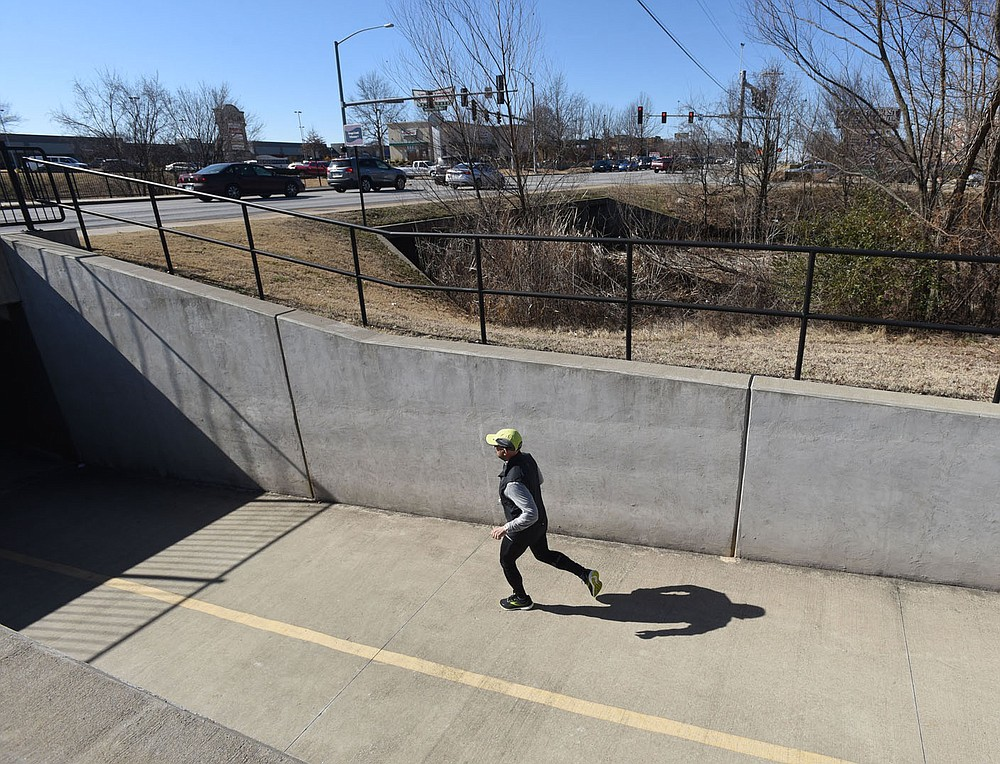 A runner moves along the Razorback Greenway on Wednesday Feb. 3 2021 near the intersetion of Medical Center Parkway and South Walton Boulevard in Bentonville. (NWA Democrat-Gazette/Flip Putthoff)