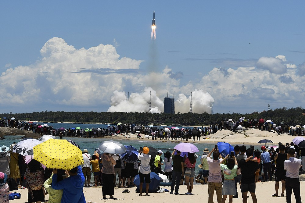 FILE - In this Thursday, July 23, 2020 photo released by China's Xinhua News Agency, spectators watch as a Long March-5 rocket carrying the Tianwen-1 Mars probe lifts off from the Wenchang Space Launch Center in southern China's Hainan Province. (Yang Guanyu/Xinhua via AP)
