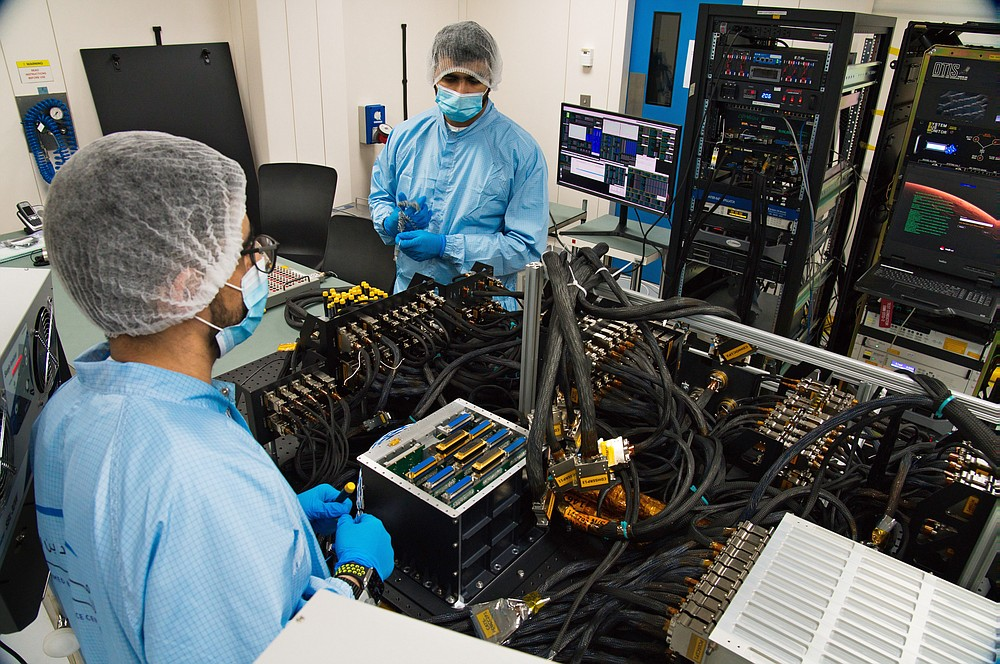 """FILE - In this Thursday, June 25, 2020 file photo, Mahmood al-Nasser, left, and Mohammad Nasser al-Emadi test the Emirates Mars Mission probe's """"flat sat"""" at the Mohammed bin Rashid Space Center in Dubai, United Arab Emirates. The spacecraft, named """"Amal,"""" Arabic for """"Hope,"""" will be the Arab world's first interplanetary mission. (AP Photo/Jon Gambrell)"""