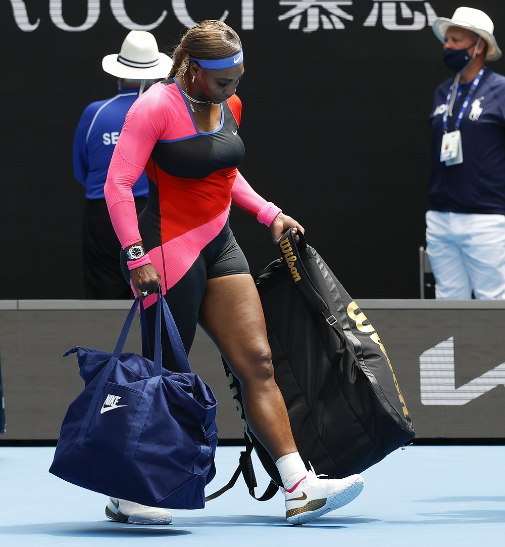 United States' Serena Williams carries her bags as she leaves th court after defeating Germany's Laura Siegemund in their first round match at the Australian Open tennis championship in Melbourne, Australia, Monday, Feb. 8, 2021.(AP Photo/Rick Rycroft)