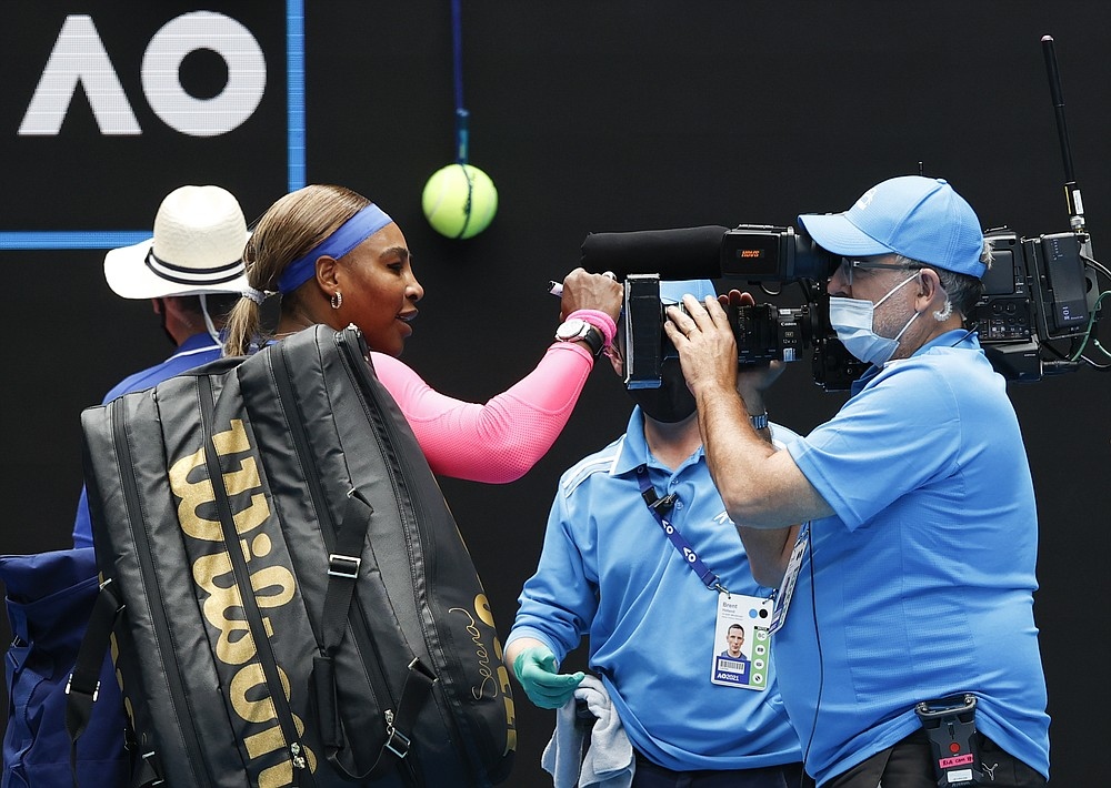 United States' Serena Williams signs the TV camera lens after defeating Germany's Laura Siegemund during their first round match at the Australian Open tennis championship in Melbourne, Australia, Monday, Feb. 8, 2021.(AP Photo/Rick Rycroft)