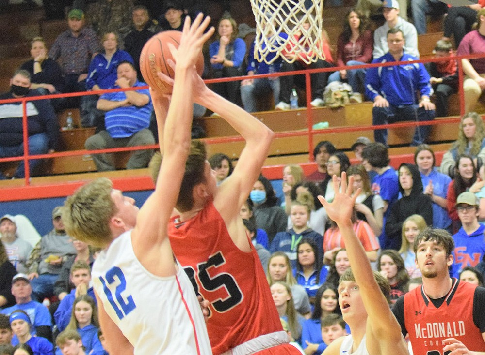 RICK PECK/SPECIAL TO MCDONALD COUNTY PRESS McDonald County's Eli McClain shoots over East Newton's Tanner Youngblood during the Patriots 75-58 win on Feb. 5 at East Newton High School.