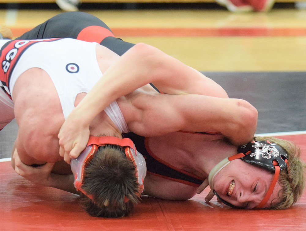 RICK PECK/SPECIAL TO MCDONALD COUNTY PRESS McDonald County's Levi Smith strains to keep from being taken to his back in his 138-pound match against Dexter Merrell of Carl Junction. Smith ended up getting the win by pin, but the Mustangs lost the dual 51-25.