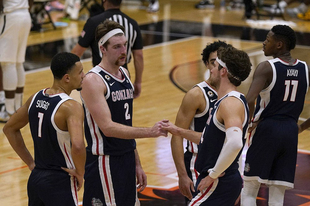 Gonzaga's Drew Timme, second from left, and Corey Kispert shake hands in the closing moments of Gonzaga's 76-58 win over Pacific in an NCAA college basketball game in Stockton, Calif., Thursday, Feb. 4, 2021. (AP Photo/Rich Pedroncelli)