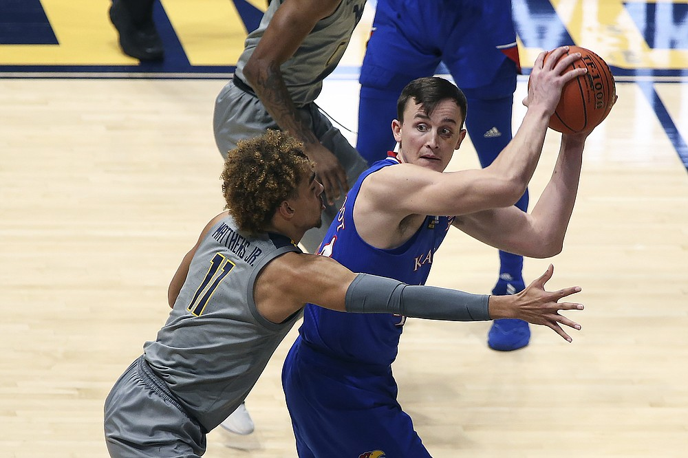 Kansas guard Latrell Jossell (4) passes while defended by West Virginia forward Emmitt Matthews Jr. (11) during the second half of an NCAA college basketball game Saturday, Feb. 6, 2021, in Morgantown, W.Va. (AP Photo/Kathleen Batten)