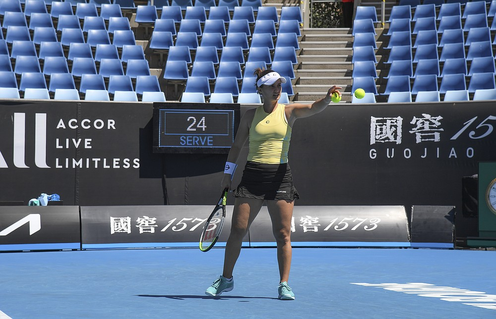 United States' Lauren Davis reaches to catch the ball as she serves to Switzerland's Belinda Bencic during their first round match at the Australian Open tennis championship in Melbourne, Australia, Tuesday, Feb. 9, 2021.(AP Photo/Andy Brownbill)