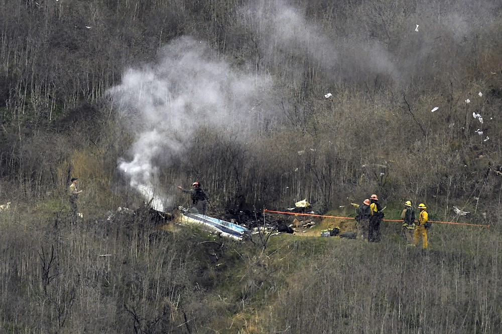 FILE - In this Jan. 26, 2020, file photo, firefighters work the scene of a helicopter crash in Calabasas, Calif. Federal safety officials are expected to vote Tuesday, Feb. 9, 2021, on what likely caused the helicopter carrying Kobe Bryant, his 13-year-old daughter and seven others to crash into a Southern California hillside last year, killing all aboard. (AP Photo/Mark J. Terrill, File)