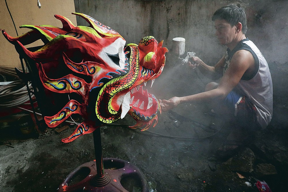 Robert Sicat sprays a protective coating on a Dragon head at a creekside slum at Manila's Chinatown, Binondo Philippines on Feb. 4, 2021. The Dragon and Lion dancers won't be performing this year after the Manila city government banned the dragon dance, street parties, stage shows or any other similar activities during celebrations for Chinese New Year due to COVID-19 restrictions leaving several businesses without income as the country grapples to start vaccination this month. (AP Photo/Aaron Favila)