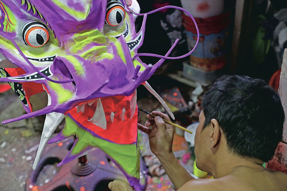 Robert Sicat paints a Dragon's head for a client outside their creekside house at Manila's Chinatown, Binondo, Philippines on Feb. 3, 2021. The Dragon and Lion dancers won't be performing this year after the Manila city government banned the dragon dance, street parties, stage shows or any other similar activities during celebrations for Chinese New Year due to COVID-19 restrictions leaving several businesses without income as the country grapples to start vaccination this month. (AP Photo/Aaron Favila)