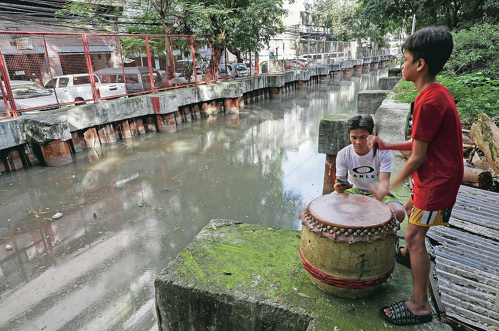Carlo Sicat, left, uses his smartphone to record the drum beat while his son Gian practices after a year of almost not playing due to pandemic restrictions at a creekside slum at Manila's Chinatown, Binondo, Philippines on Feb. 4, 2021. The Dragon and Lion dancers won't be performing this year after the Manila city government banned the dragon dance, street parties, stage shows or any other similar activities during celebrations for Chinese New Year due to COVID-19 restrictions leaving several businesses without income as the country grapples to start vaccination this month. (AP Photo/Aaron Favila)