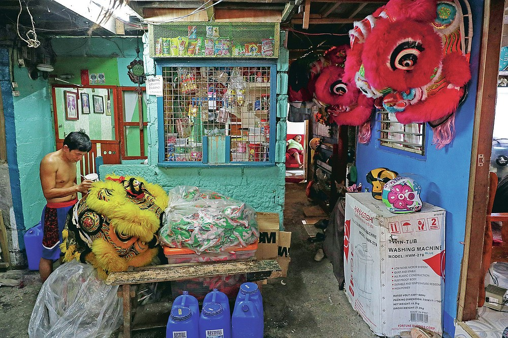 Robert Sicat paints a lion head as members of a Dragon and Lion dance group seek other ways to earn a living at a creekside slum in Manila's Chinatown, Binondo, Philippines on Feb. 4, 2021. The Dragon and Lion dancers won't be performing this year after the Manila city government banned the dragon dance, street parties, stage shows or any other similar activities during celebrations for Chinese New Year due to COVID-19 restrictions leaving several businesses without income as the country grapples to start vaccination this month. (AP Photo/Aaron Favila)