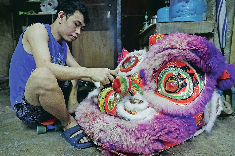 A member of a Dragon and Lion dance repair a lion's head as the group seeks other ways to earn a living at a creekside slum in Manila's Chinatown, Binondo, Philippines on Feb. 3, 2021. The Dragon and Lion dancers won't be performing this year after the Manila city government banned the dragon dance, street parties, stage shows or any other similar activities during celebrations for Chinese New Year due to COVID-19 restrictions leaving several businesses without income as the country grapples to start vaccination this month. (AP Photo/Aaron Favila)