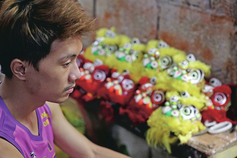 Jhayvee Sicat rests as they rush orders of miniature lion heads as members of a dragon and lion dance group seek other ways to earn a living at a creekside slum in Manila's Chinatown, Binondo, Philippines on Feb. 8, 2021. The Dragon and Lion dancers won't be performing this year after the Manila city government banned the dragon dance, street parties, stage shows or any other similar activities during celebrations for Chinese New Year due to COVID-19 restrictions leaving several businesses without income as the country grapples to start vaccination this month. (AP Photo/Aaron Favila)