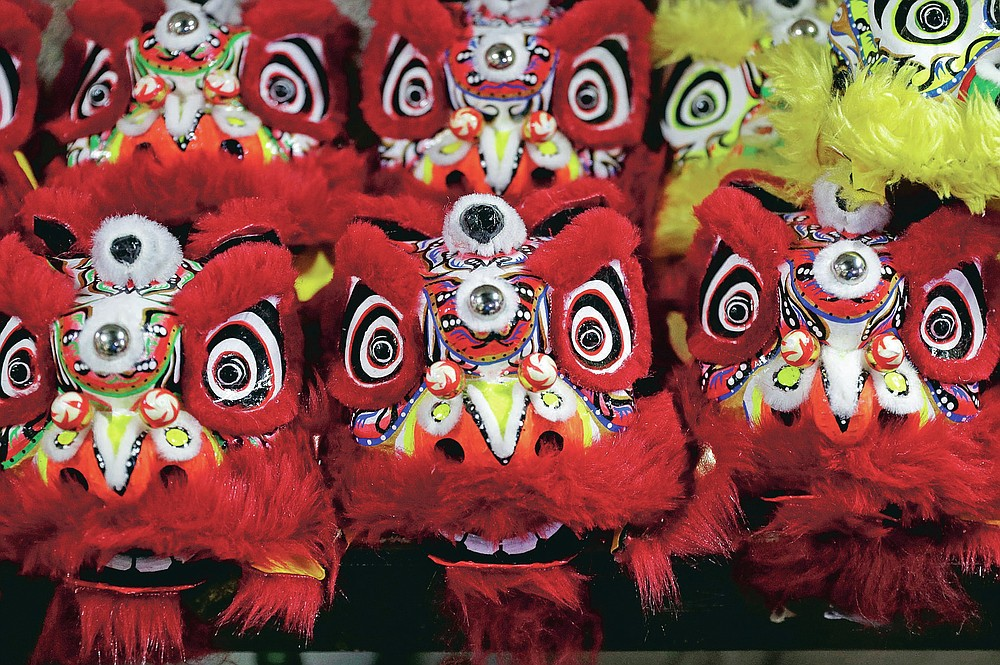 Miniature lion heads are prepared for delivery as members of a Dragon and Lion dance group seek other ways to earn a living at a creekside slum in Manila's Chinatown, Binondo, Philippines on Feb. 8, 2021. The Dragon and Lion dancers won't be performing this year after the Manila city government banned the dragon dance, street parties, stage shows or any other similar activities during celebrations for Chinese New Year due to COVID-19 restrictions leaving several businesses without income as the country grapples to start vaccination this month. (AP Photo/Aaron Favila)
