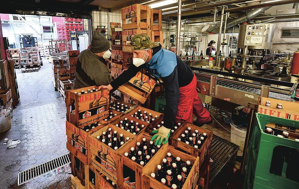 Die Mitarbeiter arbeiten in einer kleinen, familiengeführten Heller-Brauerei in Köln, Dienstag, 9. Februar 2021. Die Bars sind seit mehr als drei Monaten geschlossen, die Karnevalsfeiern wurden abgesagt und es ist nicht klar, wann sich die Situation verbessern wird.  Dies ist ein großes Problem für viele kleine deutsche Bierhersteller, die stark auf den Verkauf von Fassbier an Bars und Restaurants angewiesen sind.  (AP Foto / Martin Meissner)