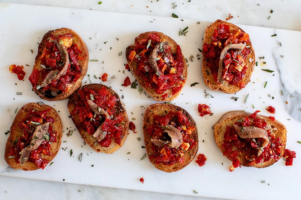 Crostini With Sun-Dried Tomato and Anchovy — The intense combination of flavors, both sweet and salty, creates an ideal savory bite. (The New York Times/Andrew Scrivani)