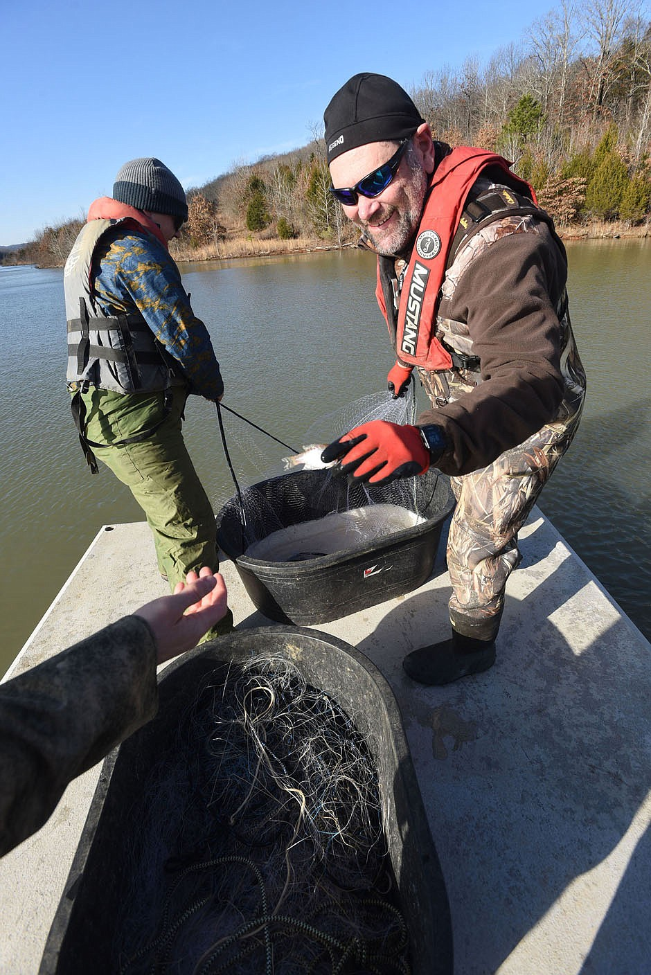Jon Stein (right), Northwest Arkansas regional fisheries supervisor for Game and Fish, takes a small crappie from the gill net. Walleye are the focus of the study at Lake Fort Smith, but Stein also looked at crappie, white bass and other species during the research. (NWA Democat-Gazette/Flip Putthoff)