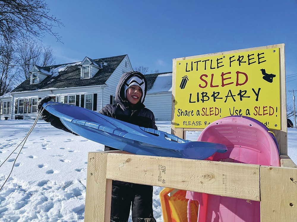 Jace Prohaska, 9, of Kansas City, Mo., borrows a sled from the Little Free Sled Library Monday morning, Jan. 25, 2021, in Ventura, Iowa. He and his brother spent hours at the sledding hill this past weekend. (Ashley Stewart/Globe-Gazette via AP)