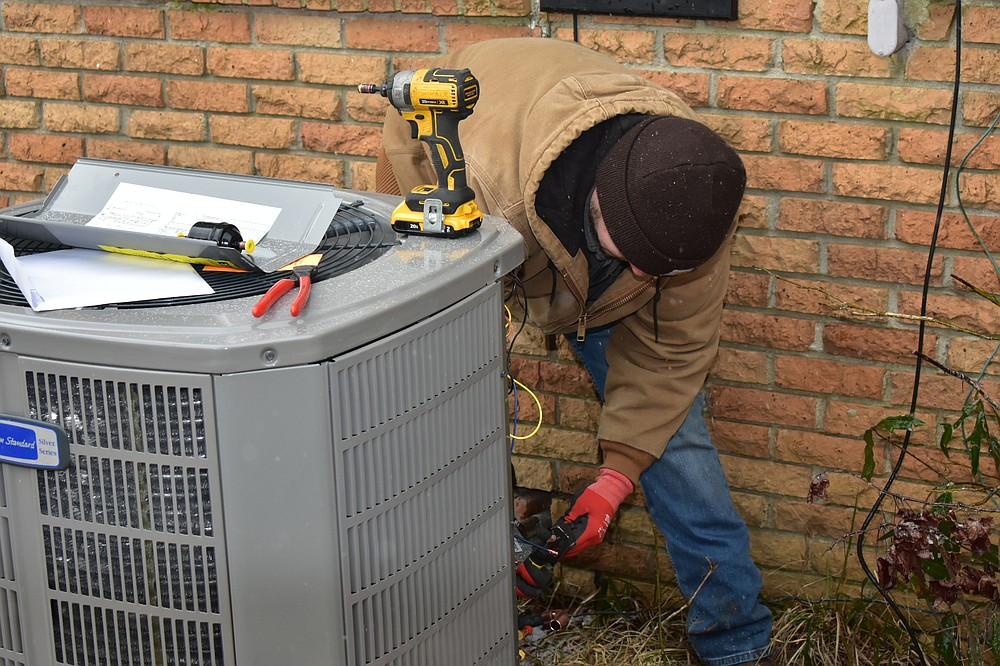 Kyle Witt, a SEARK Heating and Air technician, prepares the copper to set up a unit outside a residence on Middle Warren Road on Friday. (Pine Bluff Commercial/I.C. Murrell)