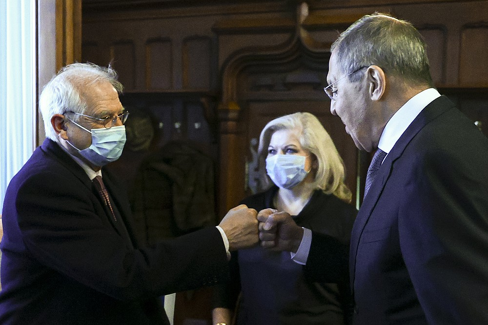 """In this photo released by the Russian Foreign Ministry Press Service, Russian Foreign Minister Sergey Lavrov, right, and High Representative of the EU for Foreign Affairs and Security Policy Josep Borrell wearing a face mask to protect against coronavirus, greet each other prior to their talks in Moscow, Russia, Friday, Feb. 5, 2021. The European Union's top diplomat expressed hopes Friday that the COVID-19 vaccine developed by Russia will soon be used across the 27-nation bloc. During a visit to Moscow, EU foreign affairs chief Josep Borrell said the Sputnik V vaccine is """"good news for the whole mankind."""" (Russian Foreign Ministry Press Service via AP)"""