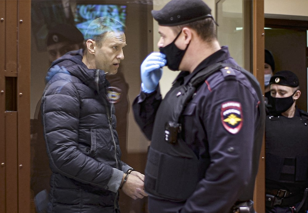 """In this photo taken taken from a footage provided by the Babuskinsky District Court on Friday, Feb. 12, 2021, Russian opposition leader Alexei Navalny, left, enters a cage to attend a hearing on charges of defamation in the Babuskinsky District Court in Moscow, Russia. Navalny was accused of slandering a World War II veteran featured in the video promoting the constitutional reform allowing to extend President Vladimir Putin's rule. The politician slammed people in the video as """"traitors"""" and stands trial on defamation charges. (Babuskinsky District Court Press Service via AP)"""