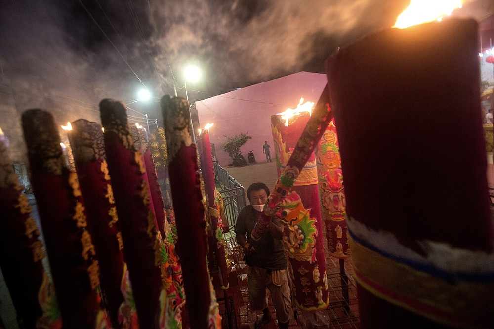 An ethnic Chinese man wearing lights joss stick during the Lunar New Year celebration at a temple in Medan, North Sumatra, Indonesia, Friday, Feb. 12, 2021. (AP Photo/Binsar Bakkara)