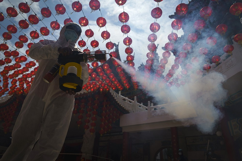 A worker disinfects the Thean Hou Temple during during first day of Chinese Lunar New Year celebrations in Kuala Lumpur, Friday, Feb. 12, 2021. The movement control order (MCO) currently enforced across the country to help curb the spread of the coronavirus, has been extended to Feb. 18, effectively covering the Chinese New Year festival that falls on Feb. 12 this year. (AP Photo/Vincent Thian)