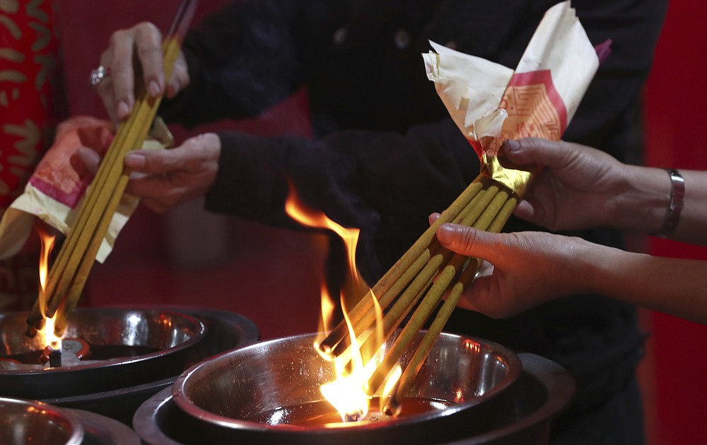 Ethnic Chinese worshippers light joss sticks during the Lunar New Year celebrations at a temple in the China Town area of Jakarta, Indonesia, Friday, Feb. 12, 2021. (AP Photo/Tatan Syuflana)