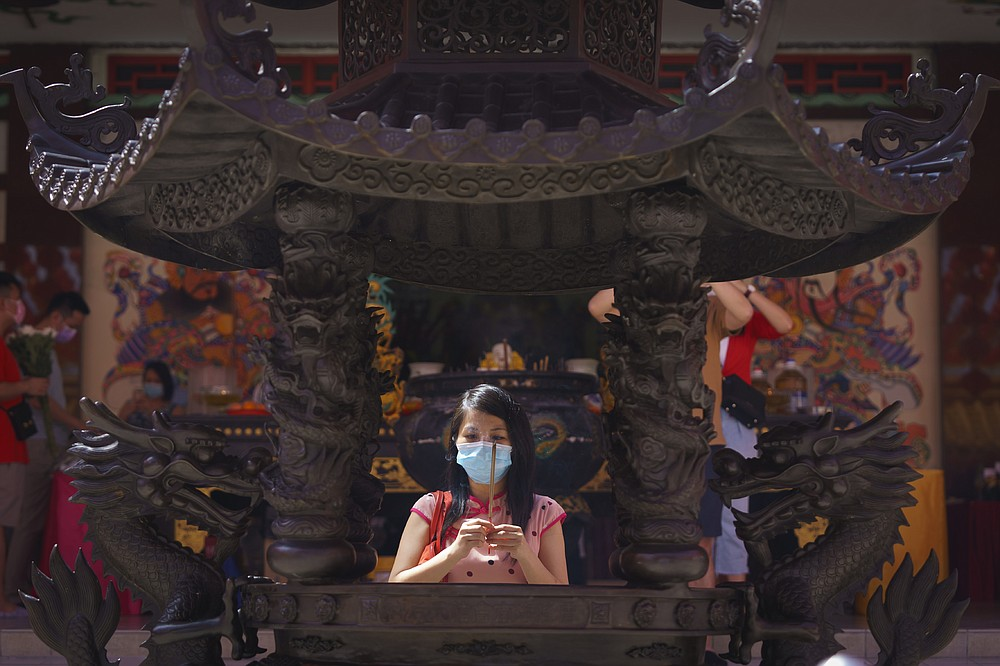 A woman wearing a protective mask prays at the Thean Hou Temple during first day of Chinese Lunar New Year celebrations in Kuala Lumpur, Friday, Feb. 12, 2021. The movement control order (MCO) currently enforced across the country to help curb the spread of the coronavirus, has been extended to Feb. 18, effectively covering the Chinese New Year festival that falls on Feb. 12 this year. (AP Photo/Vincent Thian)